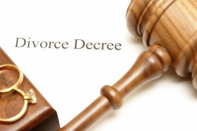 paper that says divorce decree, under a wedding ring and judge's gavel