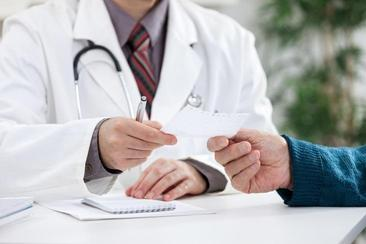 doctor handing prescription to patient