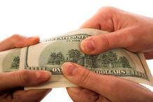 male and female hands holding hundred dollar bill