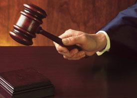 hand of male judge banging gavel on bench