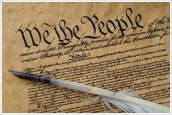 "Pen with quill lying on top of the U.S. Constitution with ""We the People"" in big letters across the top"