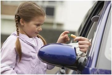 man in passenger seat of car offering candy to a little girl