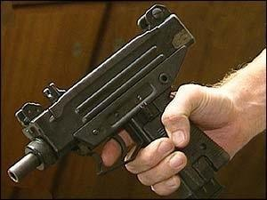 hand holding an Uzi submachine gun