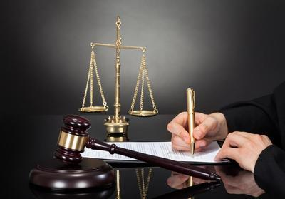 Lawyer-hand-writing-beside-scales-of-justice