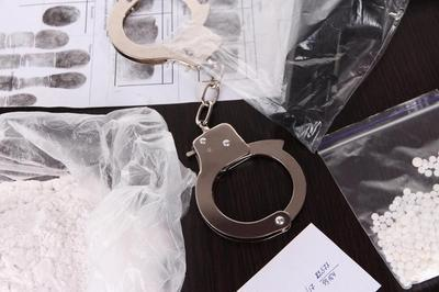 Handcuffs, fingerprints, and piles of drugs placed on top of a table