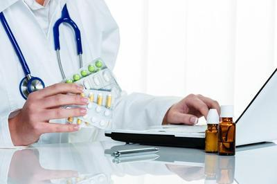 Doctor-at-laptop-holding-prescription-drugs
