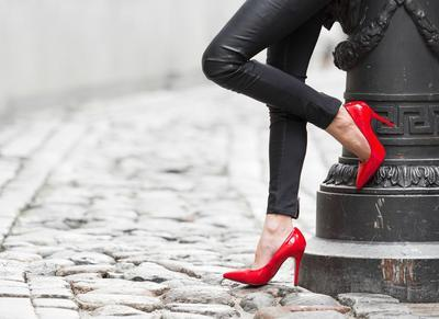 a lady with red stilettos hanging out by a light post