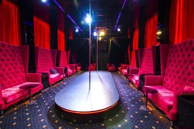 the interior of a strip club featuring a pole on stage
