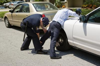 police patting down a male suspect bent over a car