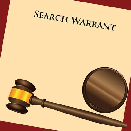 Judge's gavel placed on top of a search warrant