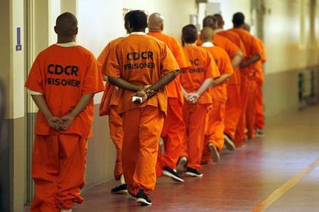 line of prisoners in orange jumpsuits