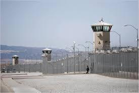 Outside of a prison, with guard tower and barbed wire
