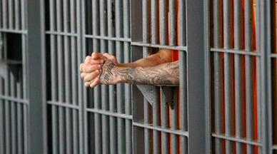 Tattooed-arms-sticking-out-of-bars-of-jail-cell