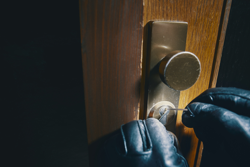 burglar with gloves on picking a lock to a front door as an example of second-degree burglary per Colorado CRS 18-4-203