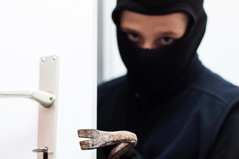 burglar in hoodie breaking into building with crowbar