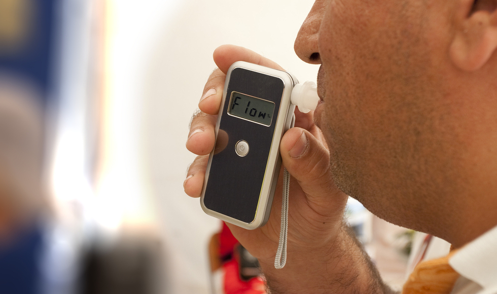 Man-blowing-into-breathalyzer
