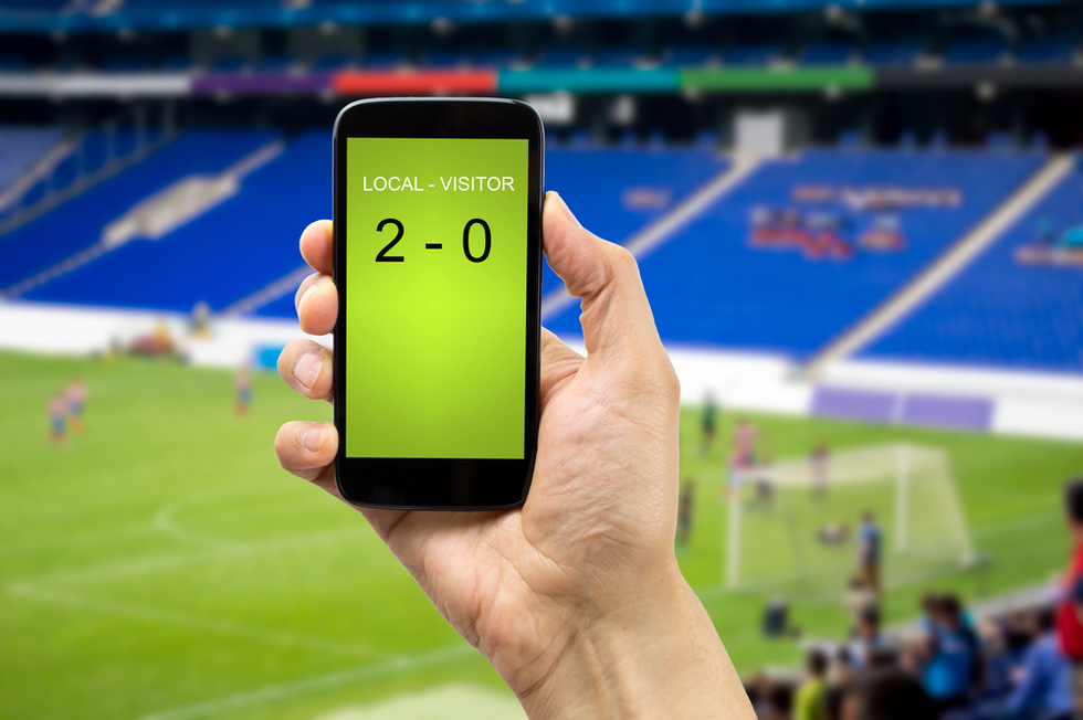 A person holding a phone to check scores
