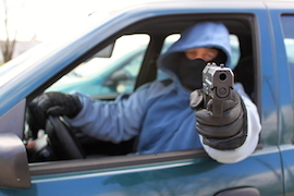 man pointing gun out car window
