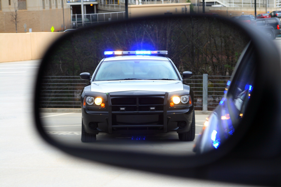 Police-car-seen-in-sideview-mirror