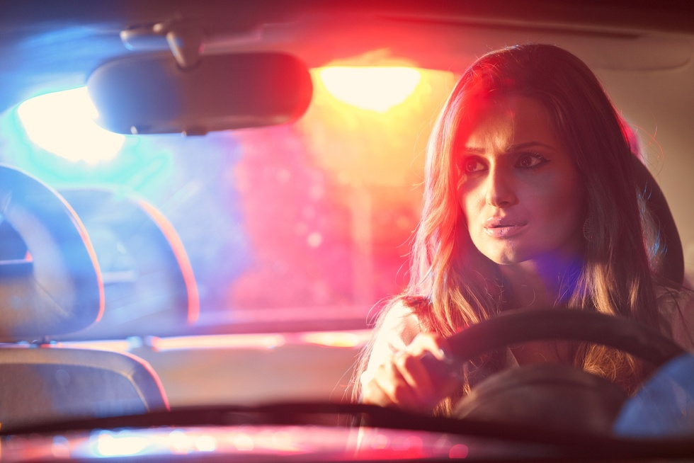Worried female driver with police lights flashing through rearview mirror