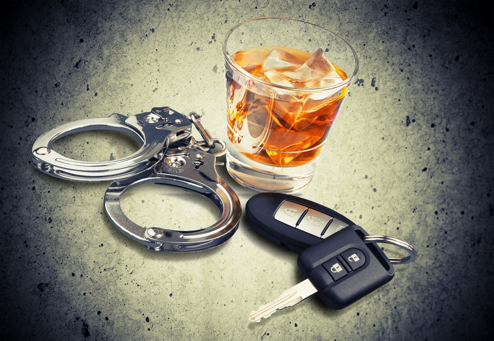 Car-keys-handcuffs-and-whiskey-representing-DUI-or-dry-reckless