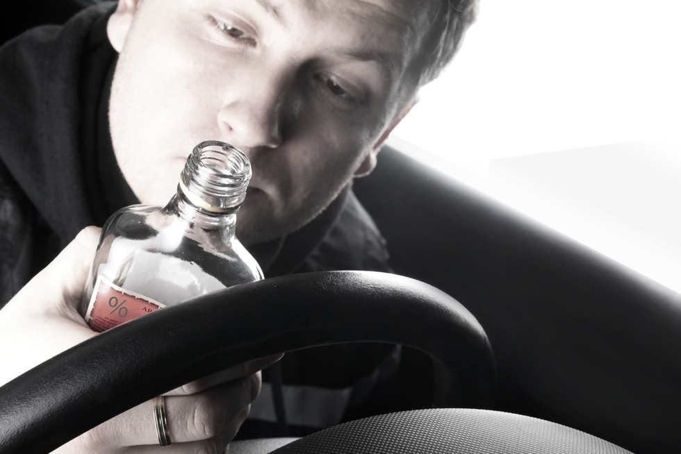 young man looking at bottle of alcohol behind the wheel of his car