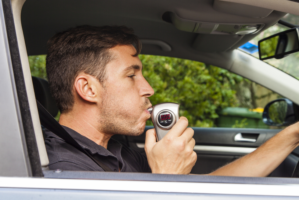 man blowing into handheld DUI breath testing device