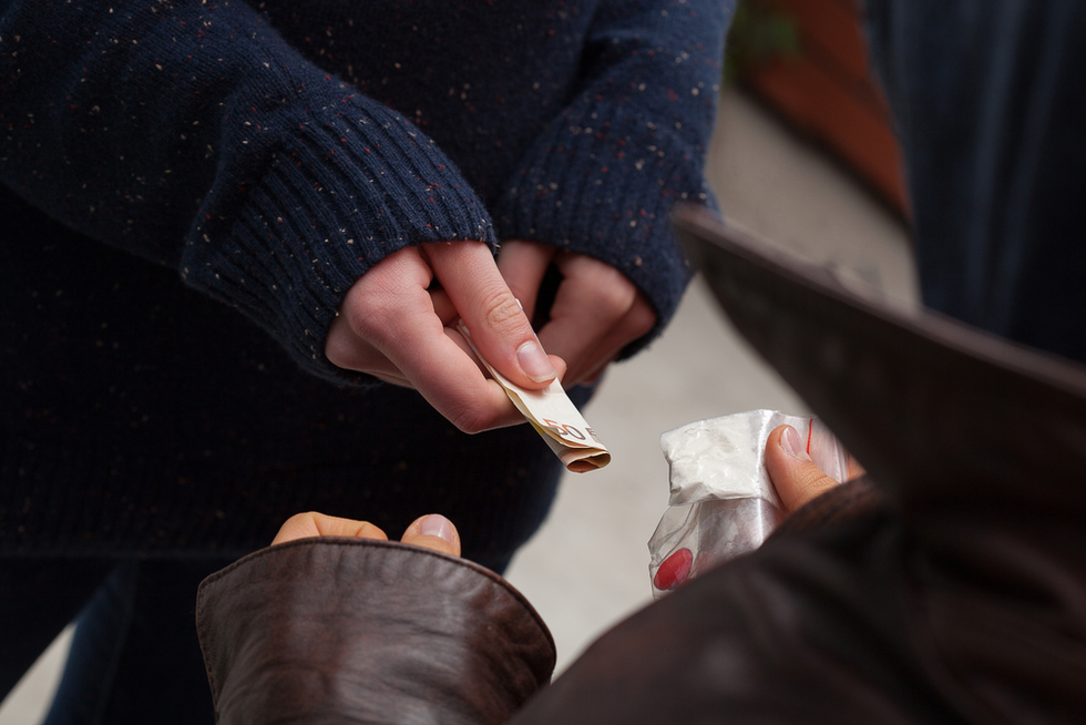 someone exchanging cash for a baggie of drugs