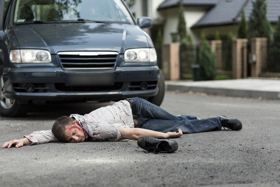 accident victim lying in front of car