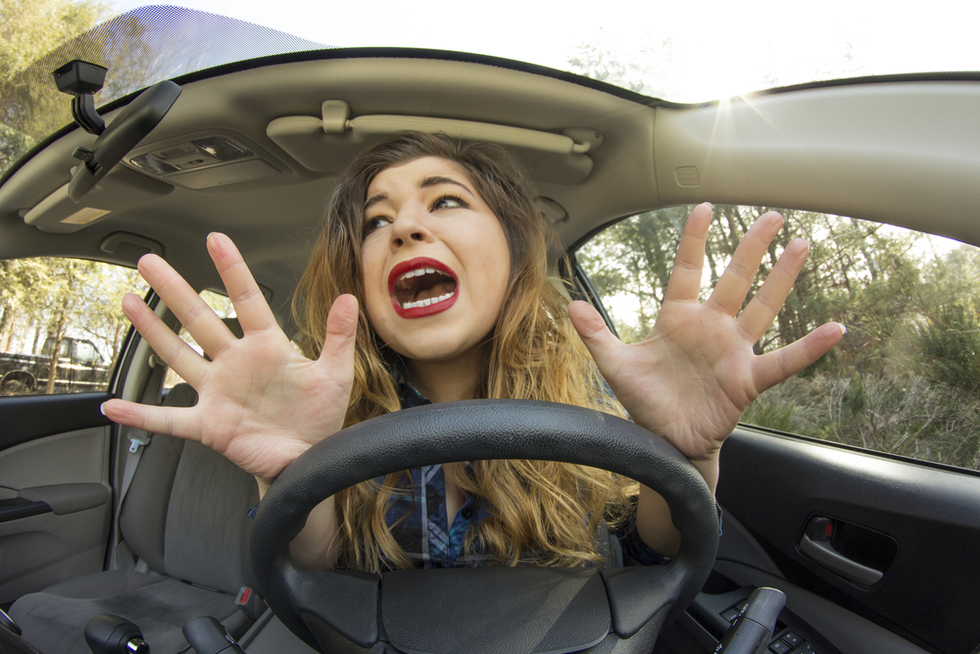 young woman driving with her hands off the wheel