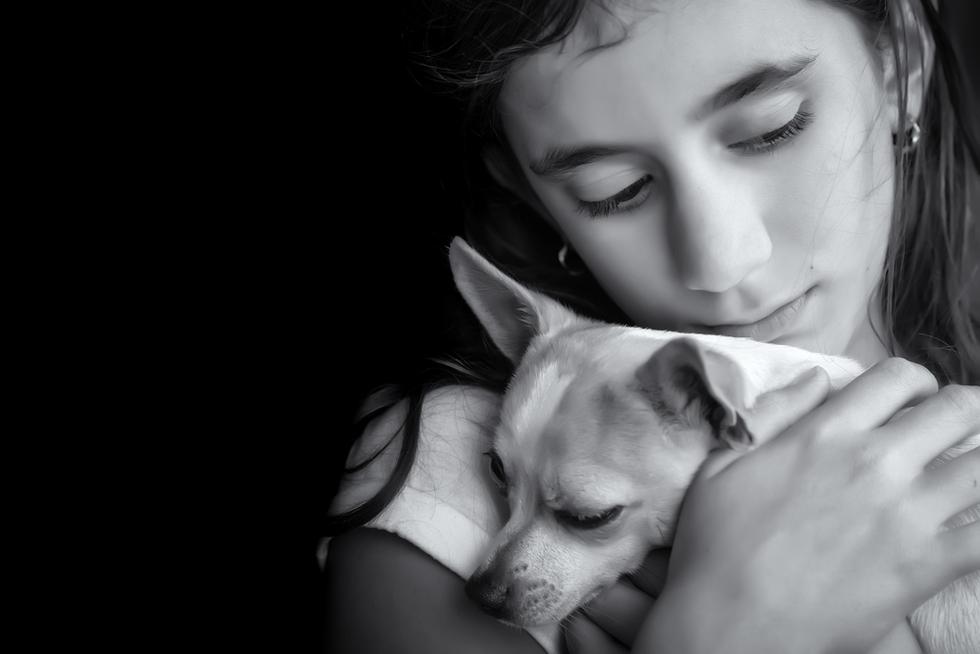sad girl holding puppy