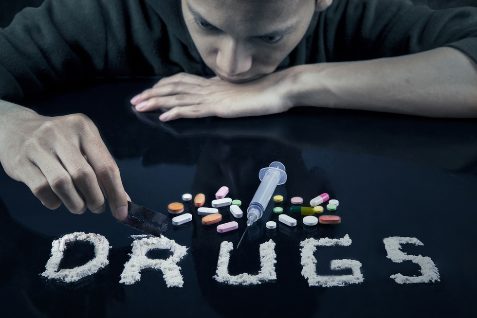 "young man with pills, a hypodermic need and cocaine spelling ""drugs"""