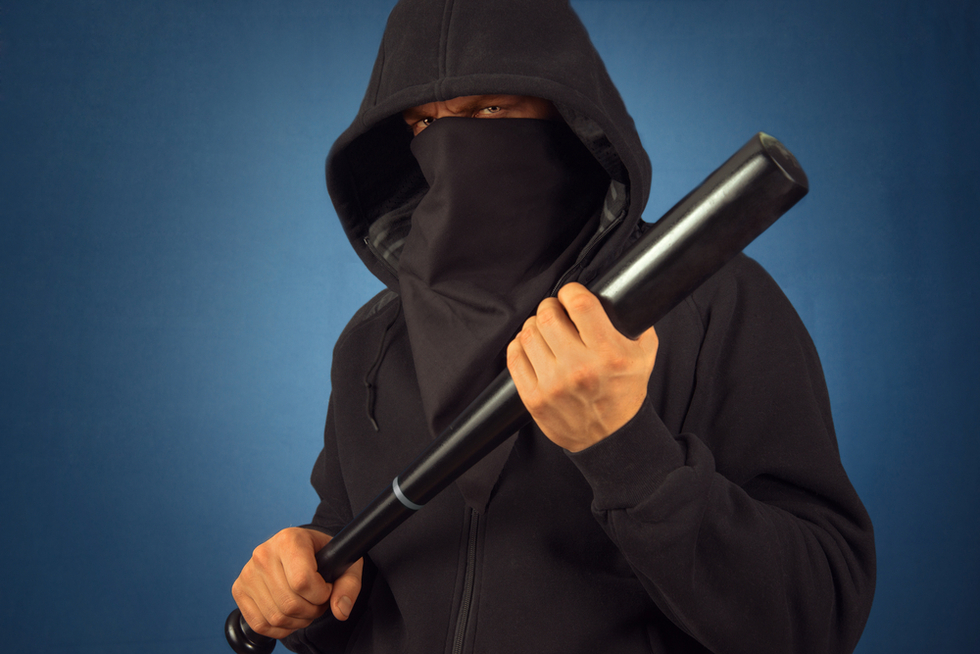man in black hoodie holding baseball bat in threatening manner
