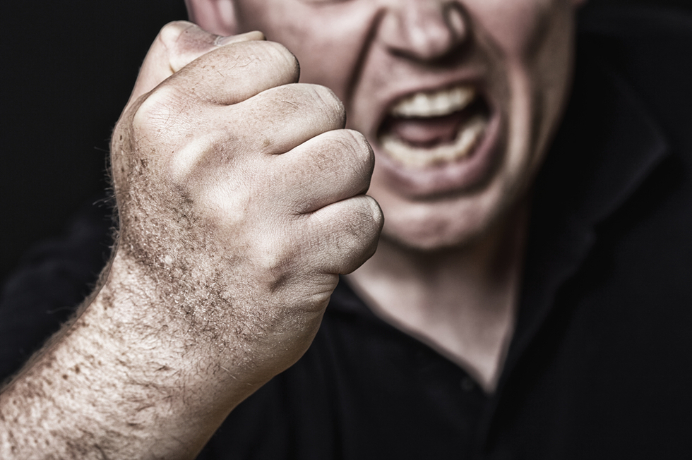 man making fist and threatening face