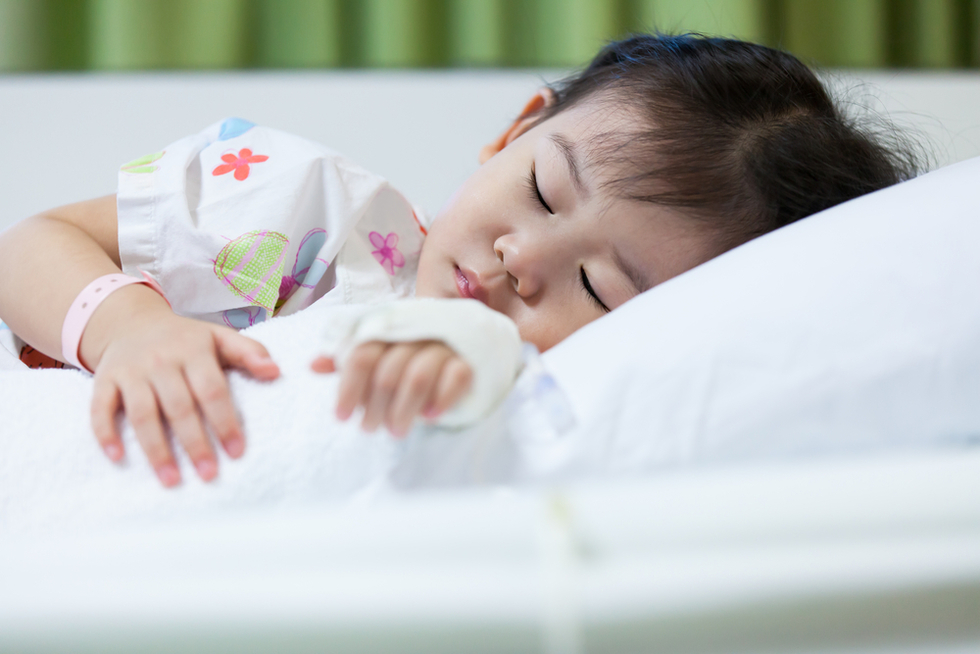 Young Asian girl lying in a hospital bed