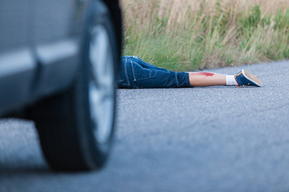 car with legs of accident victim sticking out behind it