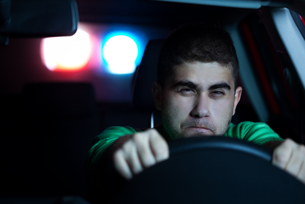 front view of young male driver behind wheel with police lights in background