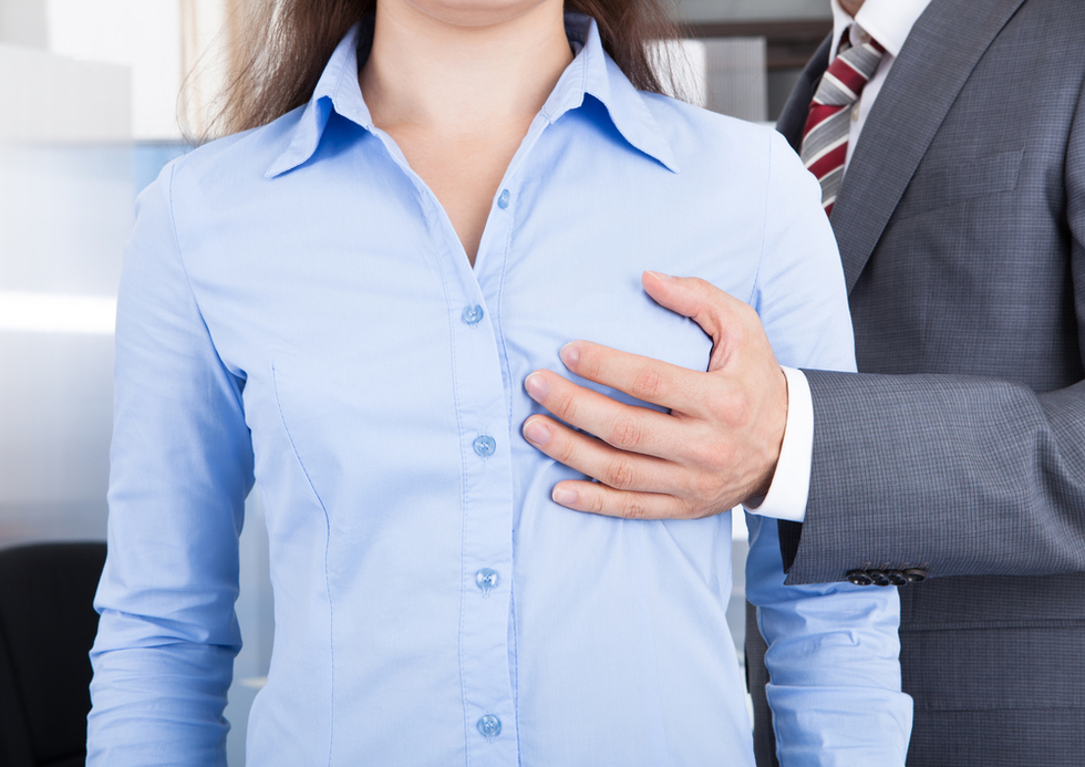 businessman touching a woman's breast through her blouse
