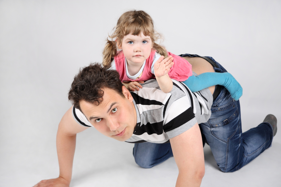 man on all fours with young girl on his back