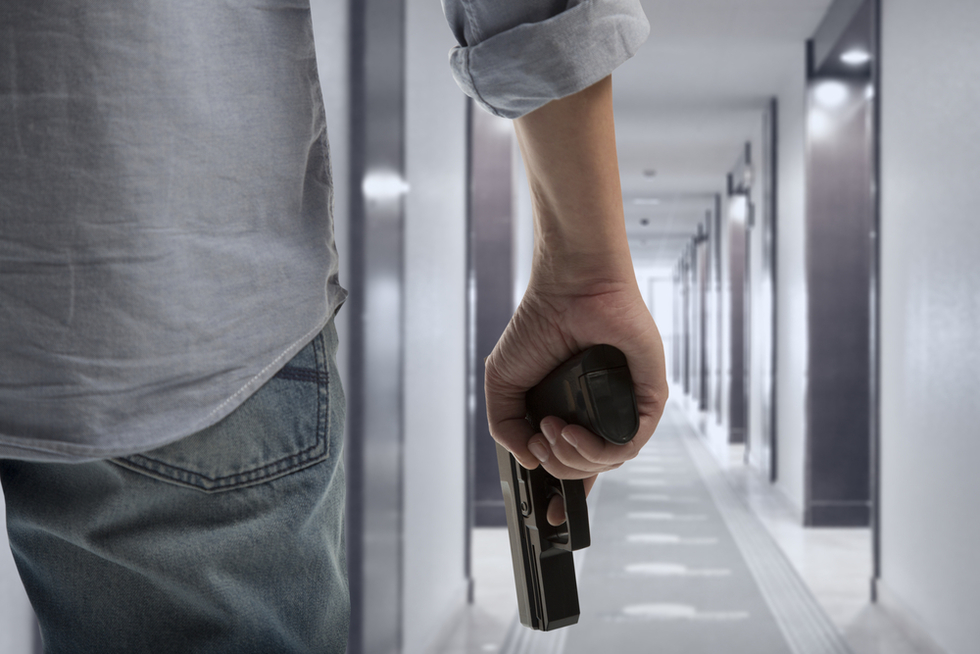 man walking down office corridor holding a gun at his side