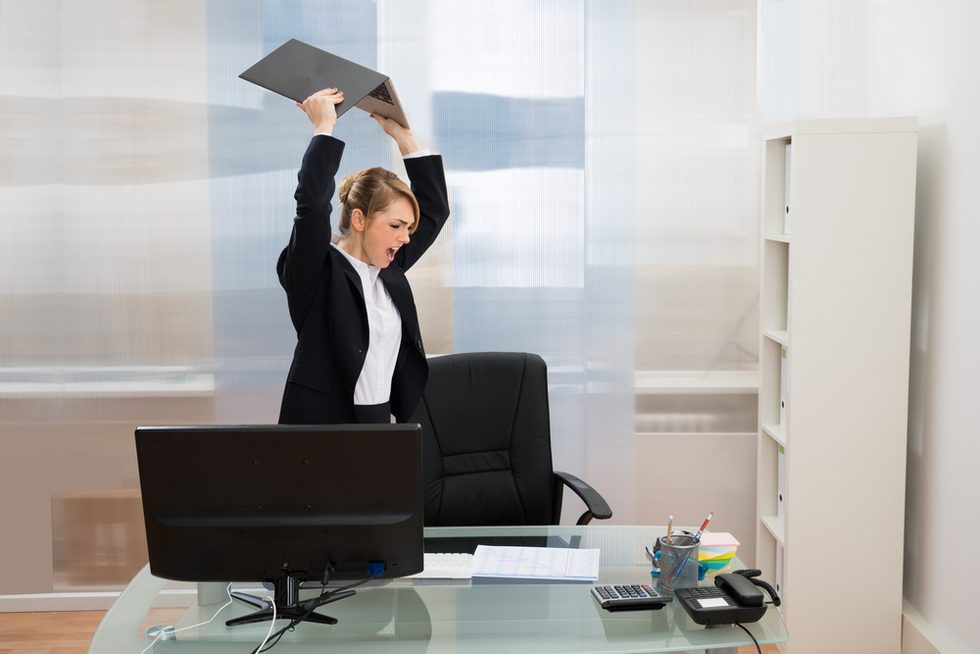 businesswoman smashing laptop computer in office