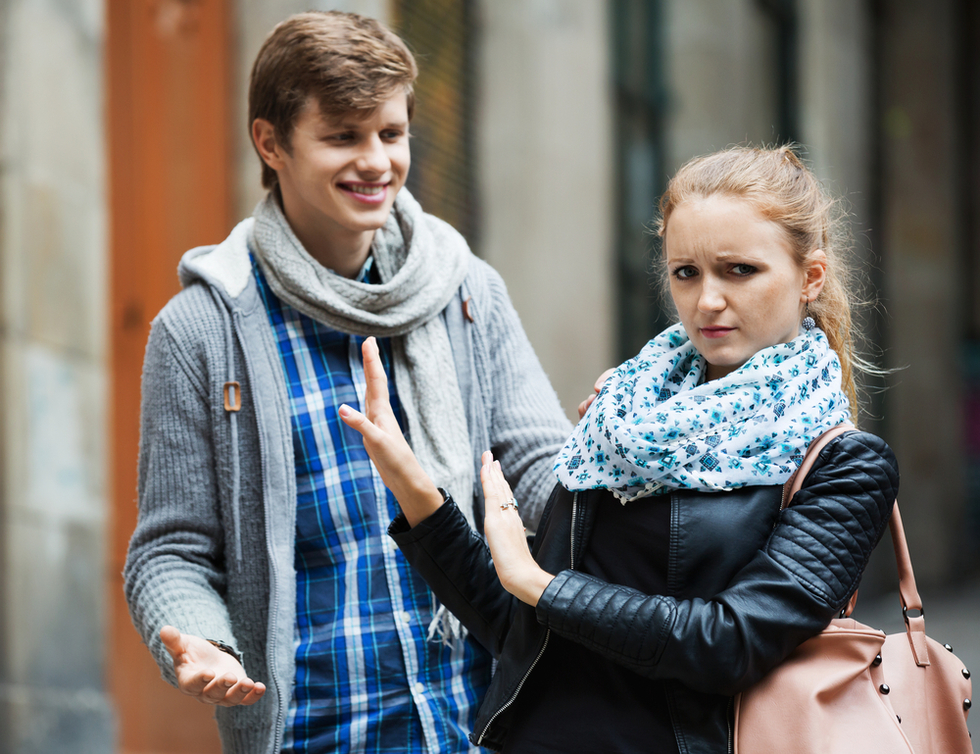 young man harassing young woman on street