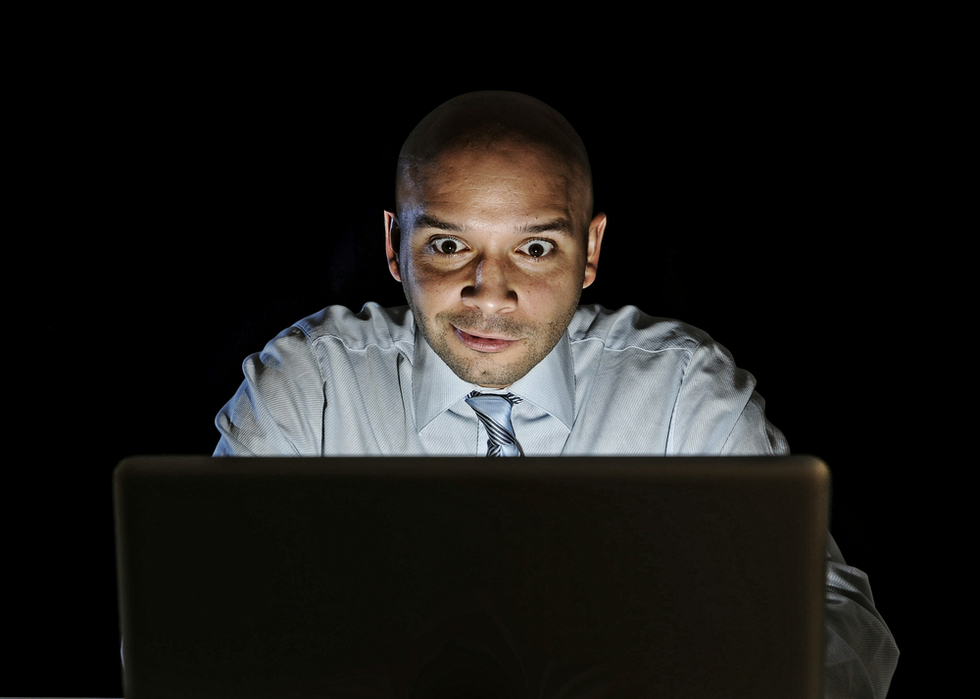 Businessman sitting behind computer looking very exicited