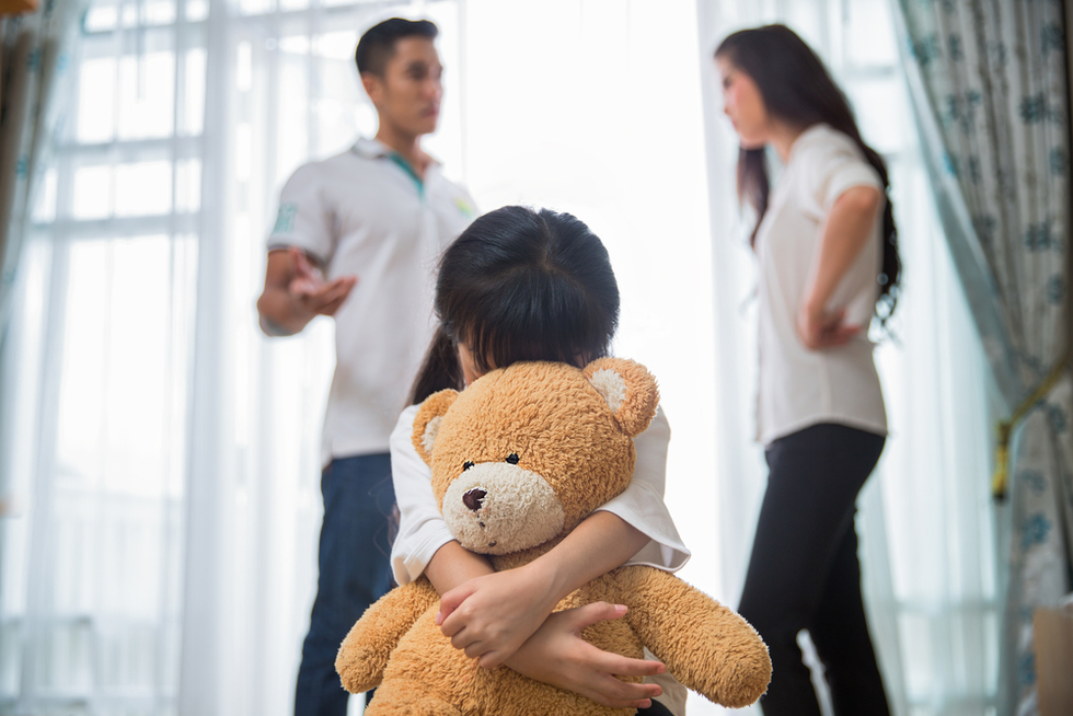child holding teddy bear while parents argue