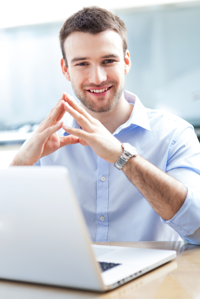 smiling man sitting behind his computer