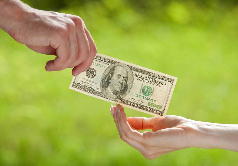 man's hand giving one hundred dollars to woman's hand