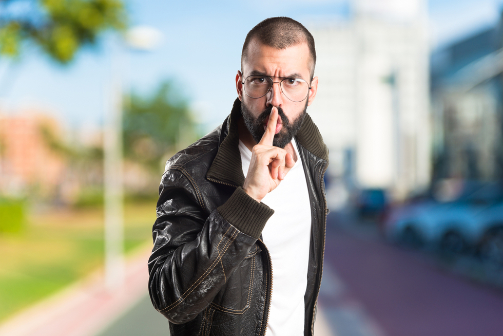 "bearded man in leather jacket making ""shushing"" gesture"