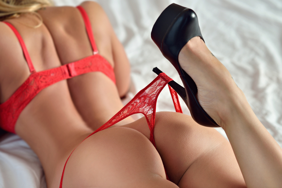 back of woman lying on bed in red bra and panties and black high heels