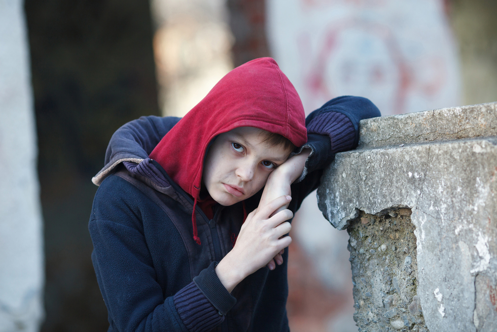 homeless boy in red hood on street
