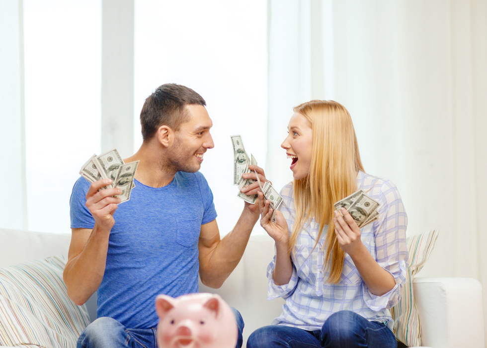 smiling couple holding lots of cash